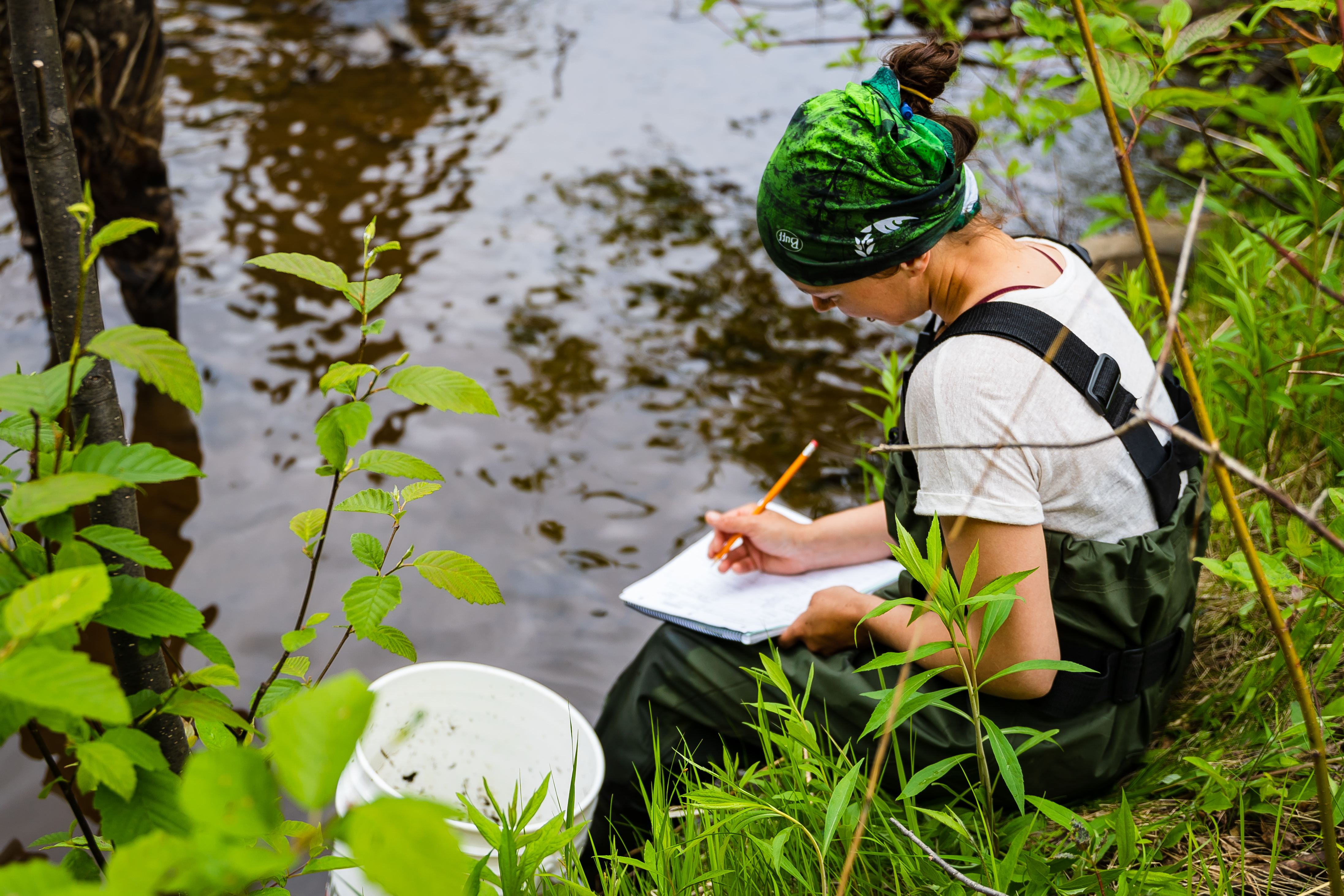 Female biology student in hip waders seated on riverbank with clipboard