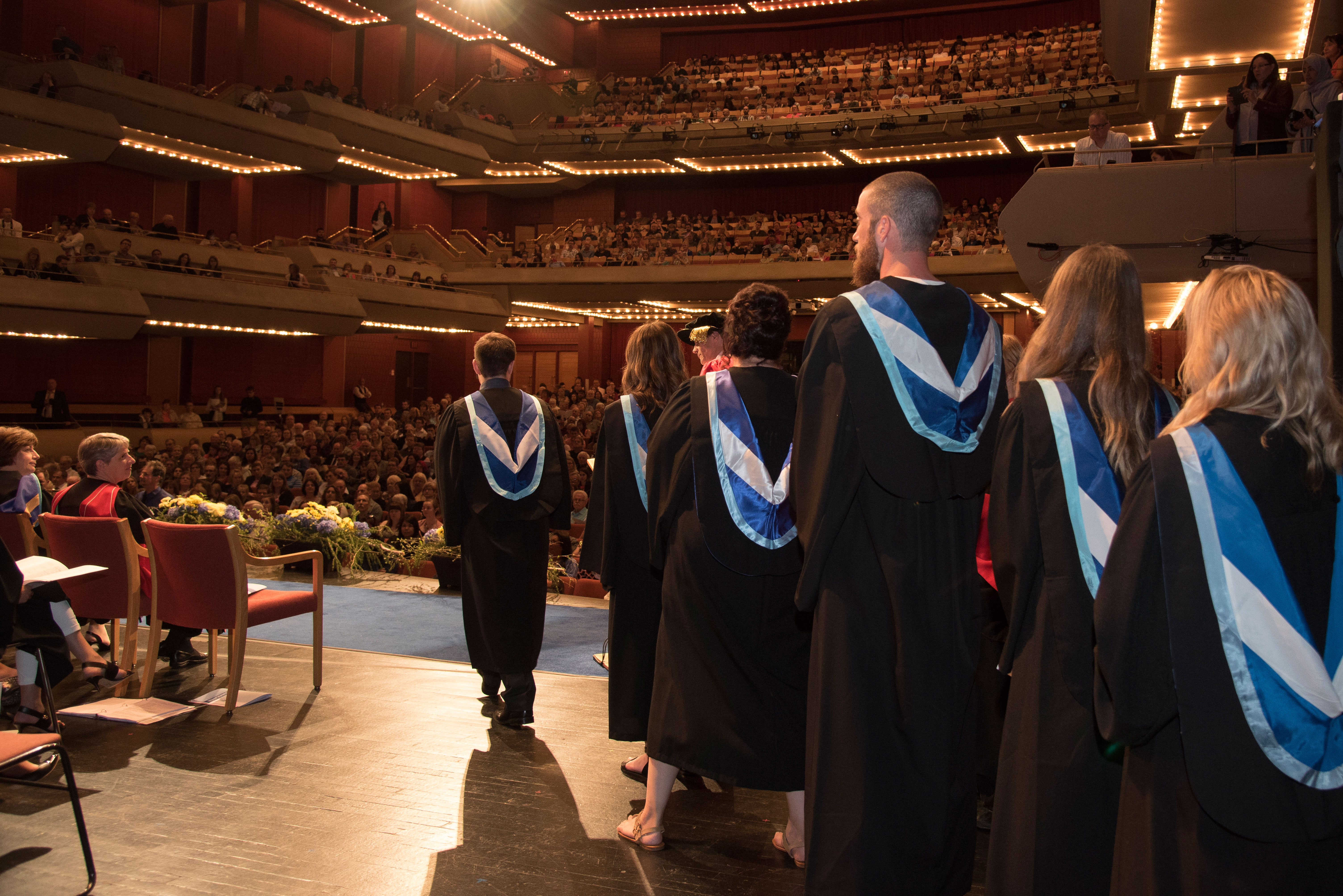 Students walking on stage during convocation ceremony