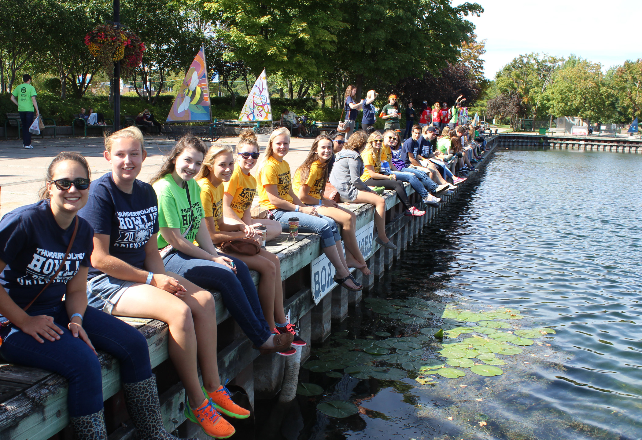 Students in downtown Orillia sitting alongside the waterfront