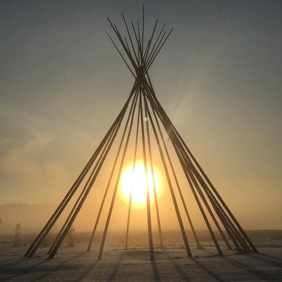 View of sunrise through the tipi poles