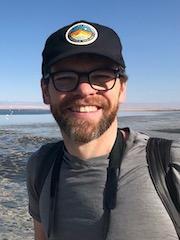 Image of Dr. Adam Algar in front of some flamingos