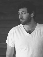 Stefan on a dark wooden background wearing a white t-shirt looking to his left