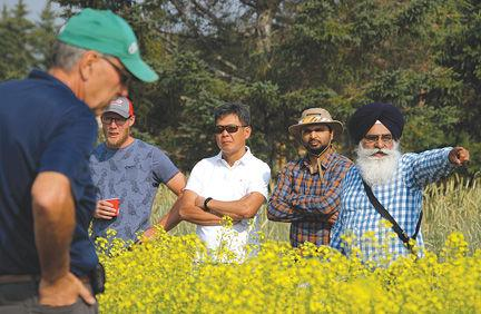 Tarlok Singh Sahota, director of Lakehead University's Agricultural Research Station, right, speaks to a tour group about some of the agricultural experiments underway.