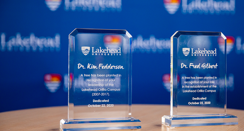 Two plaques recognizing Dr. Kim Fedderson and Dr. Fred Gilbert sit on a podium