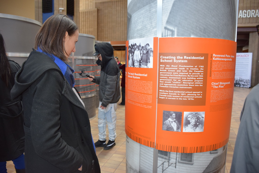 Lakehead Students reading and observing the exhibit about the Residential School System in the Agora.