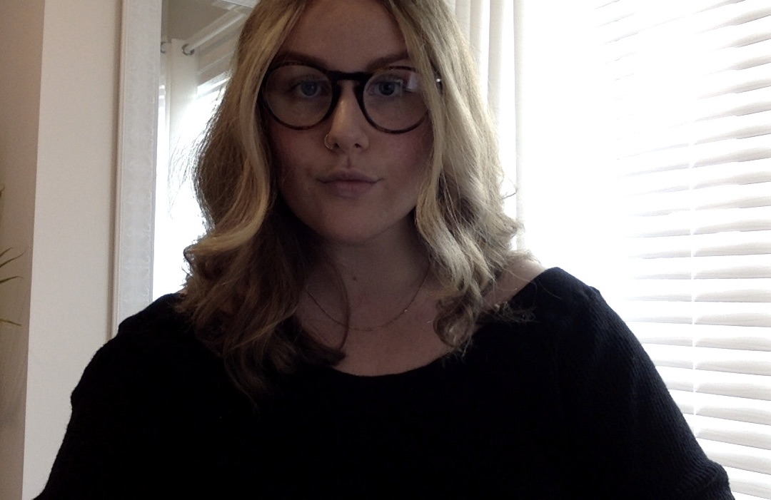 Image is of Hannah. She is wearing round, dark glasses. She has wavy, sandy-blond hair that falls shoulder-length. She is wearing a black sweater.