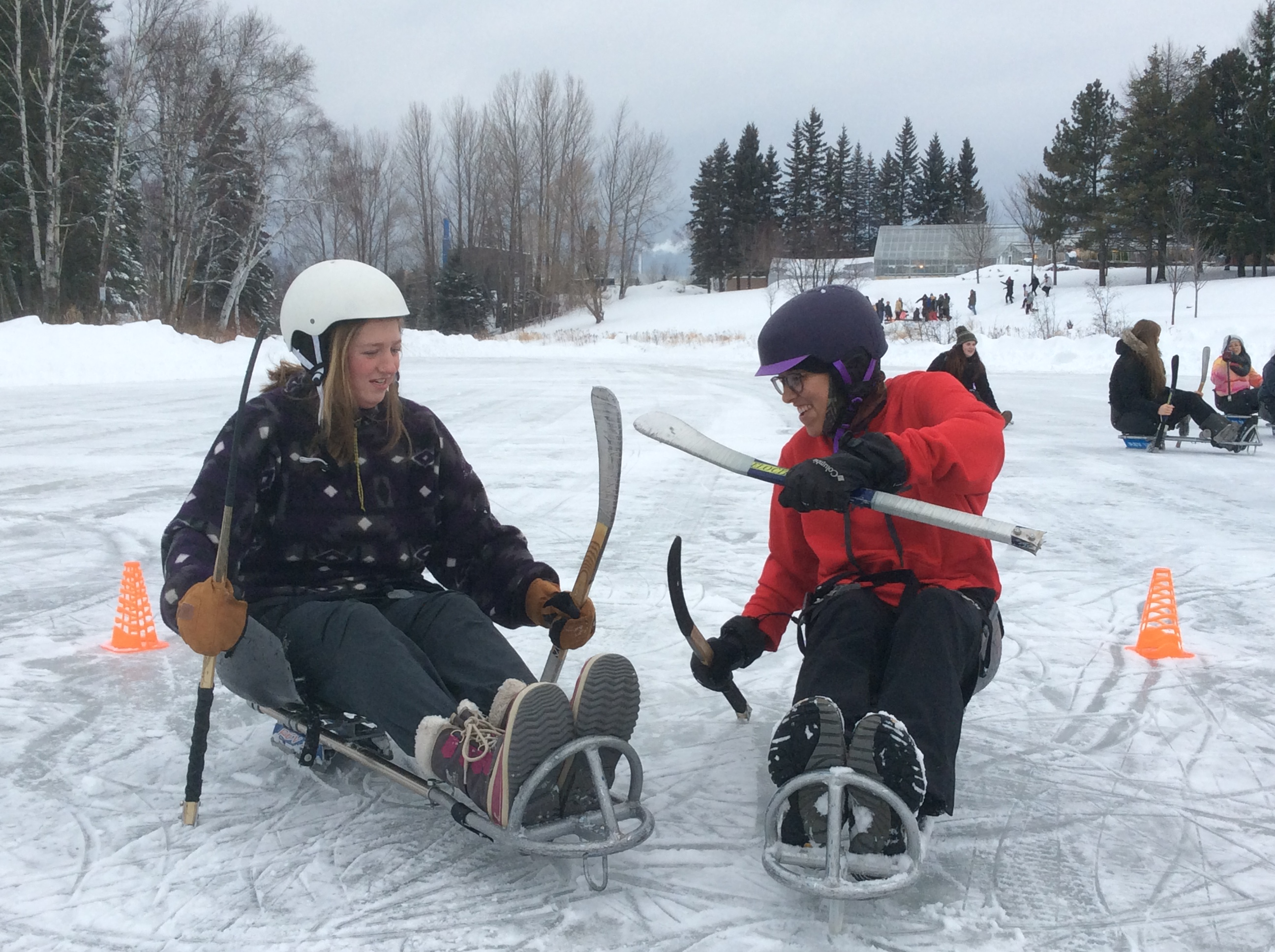 Students playing sledge hockey