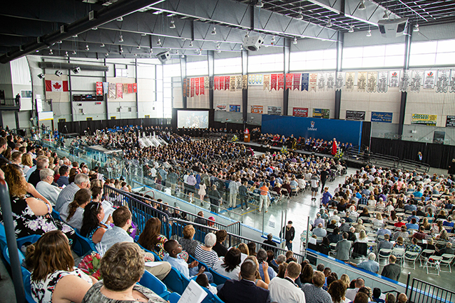 Rows of people are gathered in an arena for Lakehead University's convocation ceremony