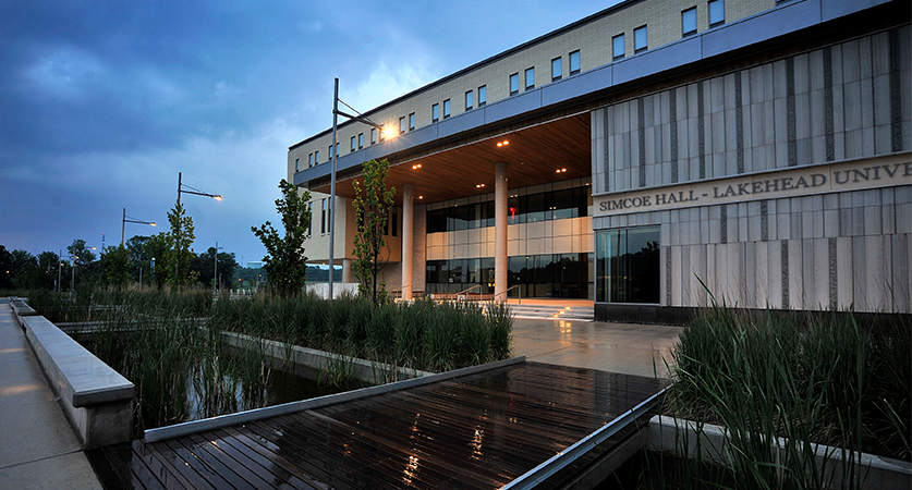 The front facade of the Orillia Campus academic building at dusk with focus on the name Simcoe Hall