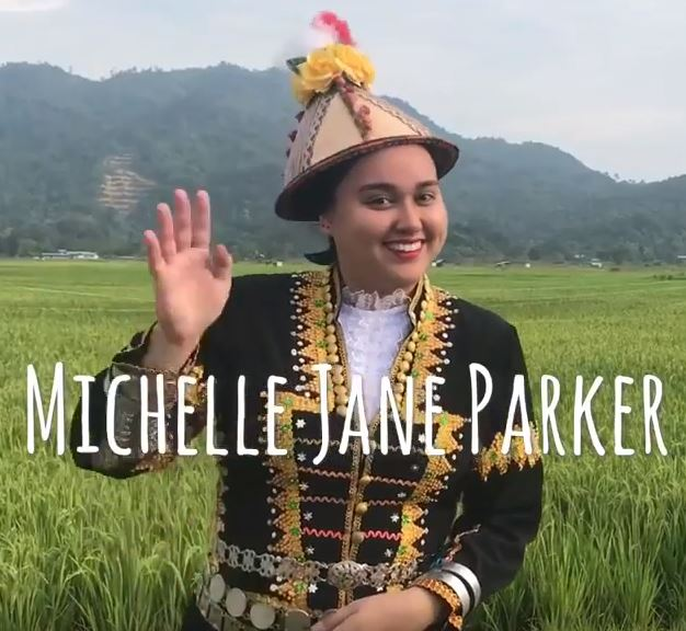 Michelle Jane Parker wearing traditional garb standing in a field smiling for the camera