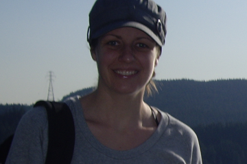Heather is wearing a hat and smiling at the camera