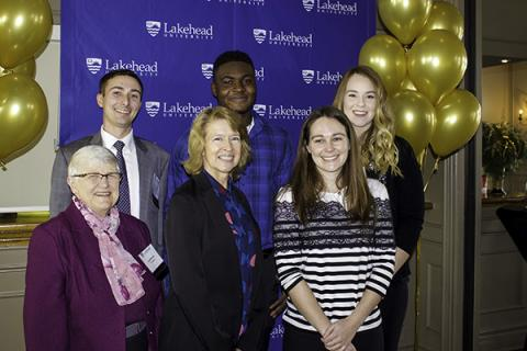 Lakehead University Chancellor Lyn McLeod and President and Vice-Chancellor Dr. Moira McPherson are pictured with alumnus Andrew Petras, current student Bolu Fabanwo, criminology program coordinator and professor Dr. Alana Saulnier, and third year criminology student and event emcee Courtney Holmes.