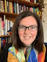Dr. Jennifer Chisholm has shoulder length, straight brown hair. She is wearing black rimmed glasses and has hazel eyes. There is a bookshelf in the background. She is wearing a black shirt and is wearing a light scarf that is red, orange, yellow, green, blue and some white.