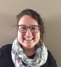 profile picture of white woman smiling, wearing glasses and scarf