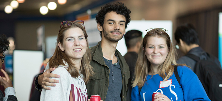 Three students smiling for the photo at a orientation event