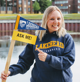 An orientation leader in front of Lake Tamblyn with a sign that says to ask her questions