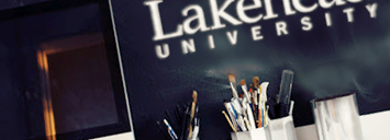 "chalkboard behind desk with ""lakehead university"" written - who can help?"