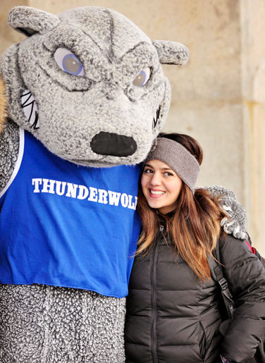 A student smiling beside our mascot Wolfie