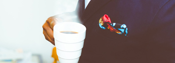 sharply dressed person holding a cup of coffee