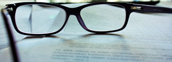 A pair of glasses on a document which symbolizes a review of something