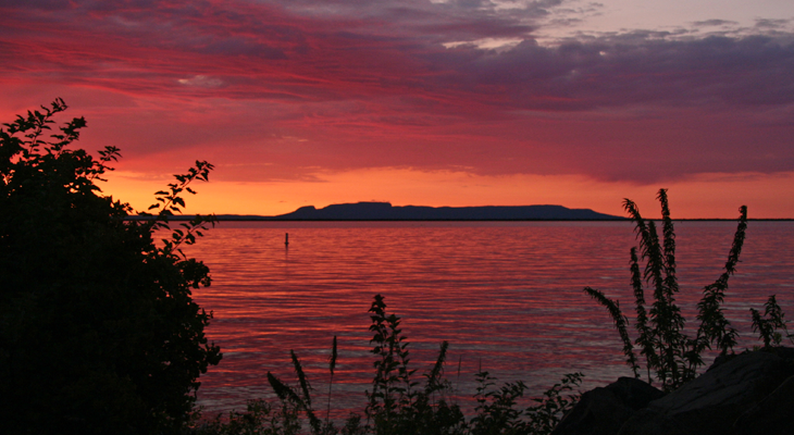A beautiful sunset  over Lake Superior in Thunder Bay with the Sleeping Giant in the background. The sky and reflection of the water is a purple to orange gradient.