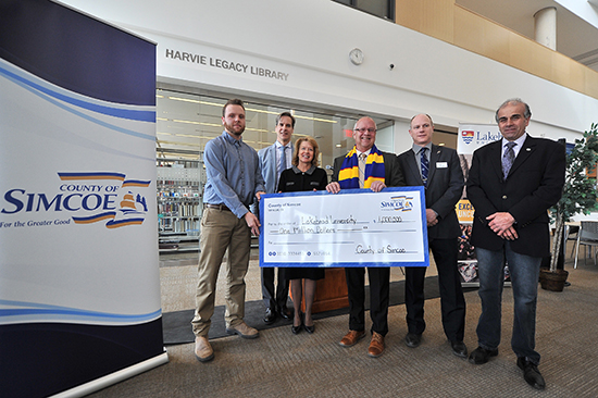 Lakehead Orillia student Cody Avery, Lakehead Orillia Principal Dr. Dean Jobin-Bevans, Lakehead Interim President and Vice-Chancellor Moira McPherson, Warden Gerry Marshall, Mayor Basil Clarke, and Mayor Mike Burkett are pictured holding a cheque for $1-million