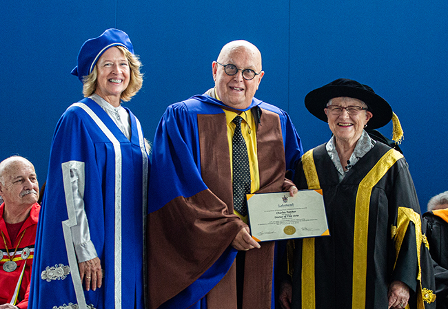 A blonde haired woman wearing blue and white regalia and a blue cap is pictured with an older gentleman in spectacles holding a certificate alongside an older woman in black and yellow regalia