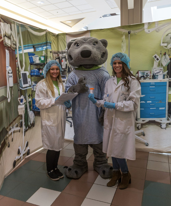 Photo of Wolfie with two people in the emergency room simulation at the Intercity Shopping Centre.