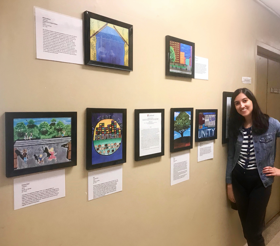 Photo of Mehdia Hassan and her students' artwork