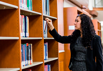 A female team member looking through the extensive Law Library