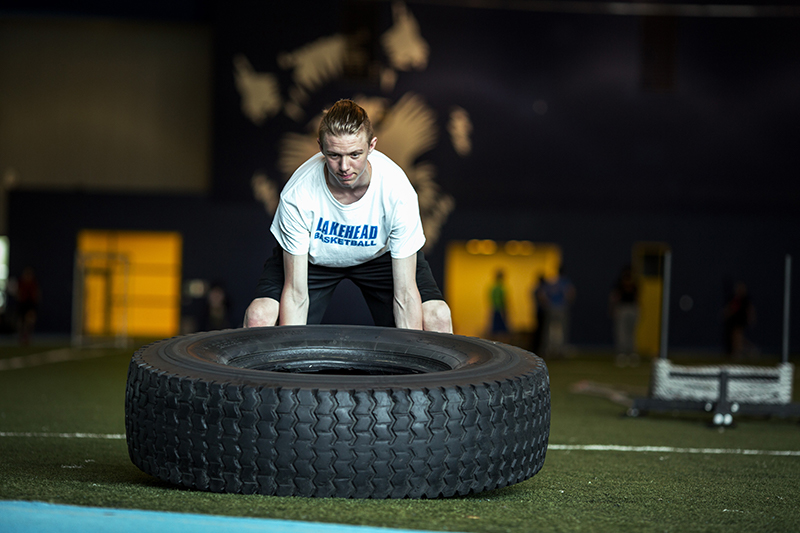 A student lifting a large tire in the Thunder Bay fieldhouse