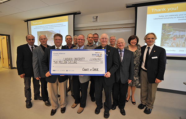 County of Simcoe Warden Gerry Marshall (centre behind cheque) presents a $2M cheque to Lakehead University President & Vice-Chancellor Dr. Brian Stevenson (holding cheque left), as Orillia Campus Principal Kim Fedderson (far right), Lakehead V.P. External Relations Deb Comuzzi, and members of County Council celebrate.