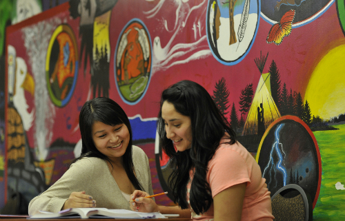 This is an image of two girls looking at a textbook while sitting at a table. Behind them is art in the woodland style.