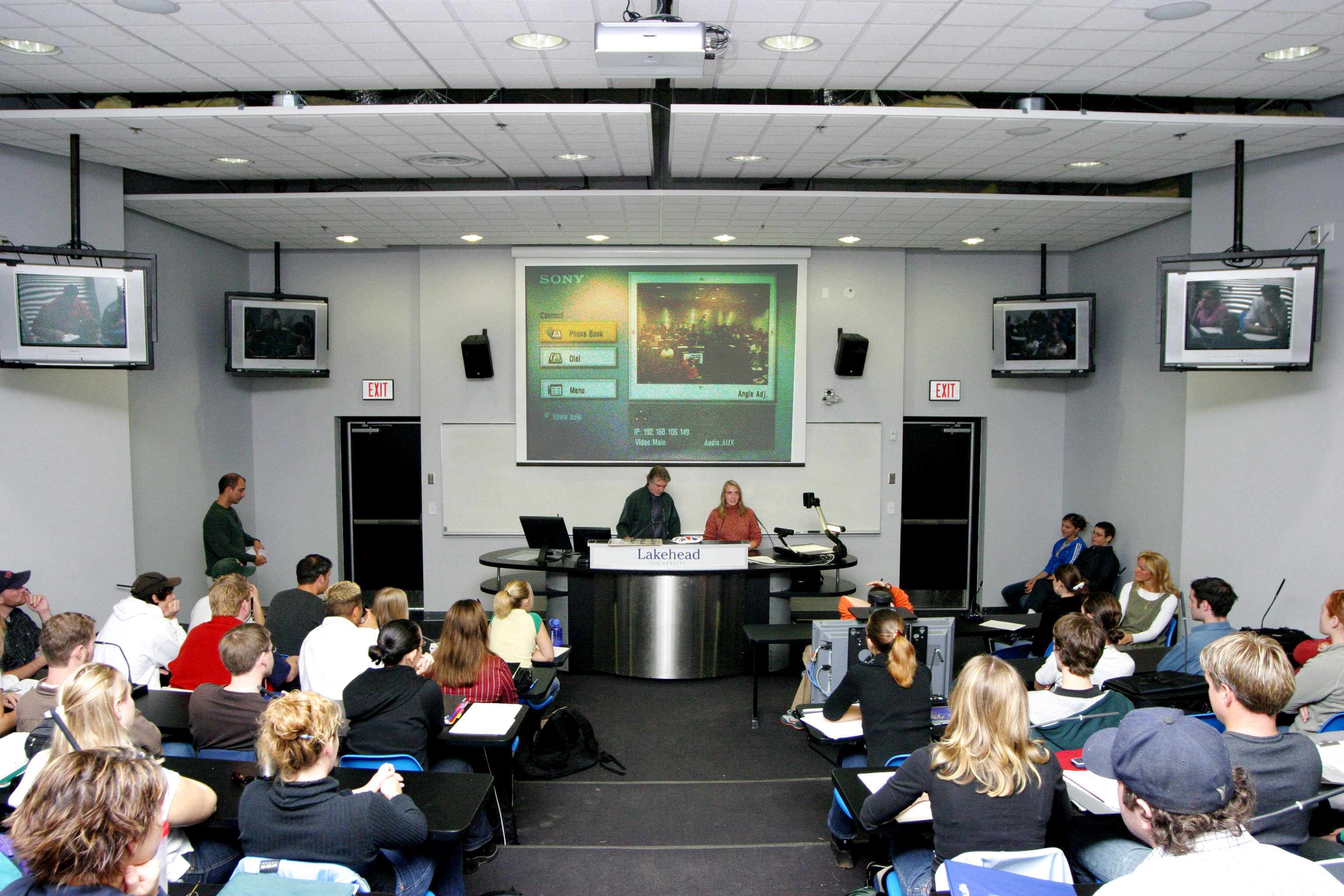 Multimedia classroom with class in session displaying use of multimedia equipment