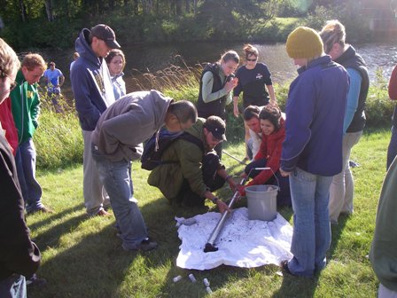 Group of students gathered around a mental rod containing water samples