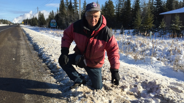 Stephen Kissin, professor emeritus with Lakehead University's geology department, checks out an area alongside Highway 61 where police suspect a meteorite may have hit the ground. (Jeff Walters/CBC)
