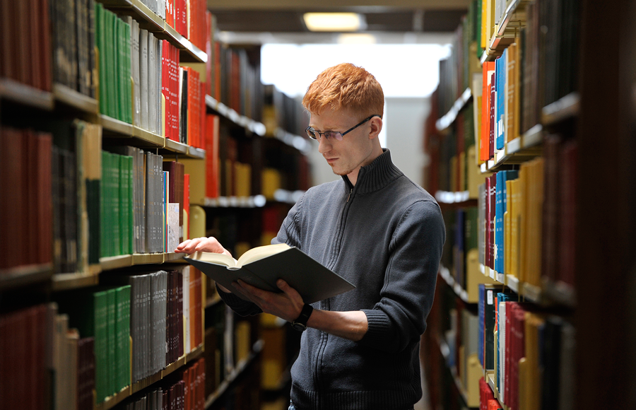 This is an image of a student looking through library resources