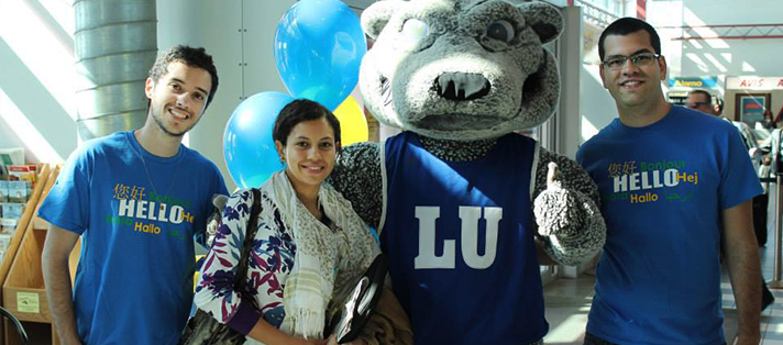 A studnet arriving at the Thunder Bay Airport and being greeted by Lakehead staff and students with wolfie