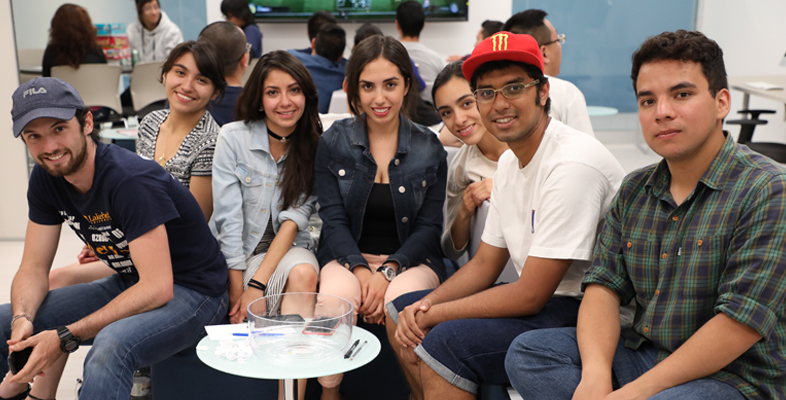 A group of young students from various parts of the world posing and smiling for the photo