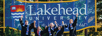 Students in graduation gowns jumping in front of Thunder Bay's main entrance signage