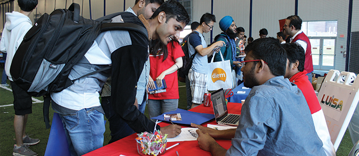 Students speaking with advisors at a fair
