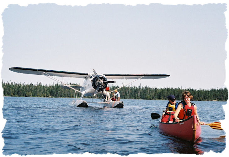 Image of a float plane unloading canoes