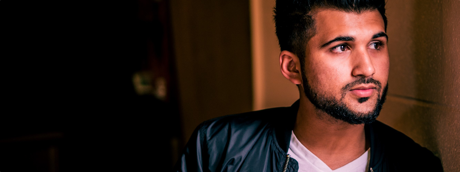 Profile view of Usama Syed in a leather jacket leaning against a wall